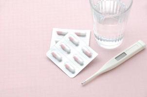 capsule en koortsthermometer met glas water foto