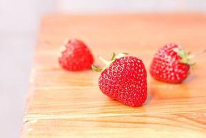 drie aardbeien op tafel, zijaanzicht foto
