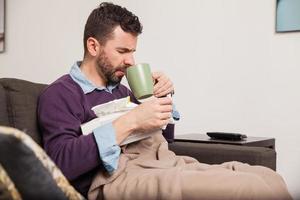 man met een verkoudheid wat thee drinken foto