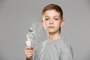 ongelukkige jongen die inhalatormasker houdt dat rook op grijze achtergrond vrijgeeft foto