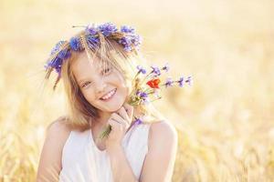 gelukkig meisje met bloemen kroon op zomer tarweveld foto