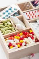medische pillen en ampullen in houten kist foto