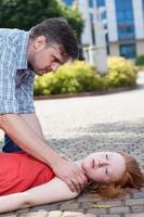man helpt bewusteloze vrouw foto