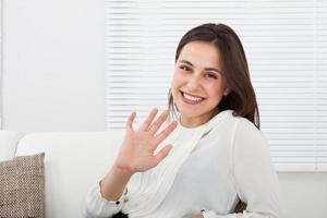 gelukkig zakenvrouw wuivende hand op sofa foto
