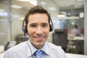 zakenman op kantoor aan de telefoon met hoofdtelefoon foto