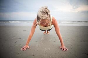 vrouw doet push-ups op het strand foto
