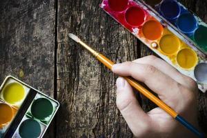 hand van de kunstenaar met een penseel om te tekenen