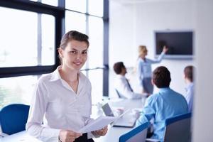 zakenvrouw met haar personeel op achtergrond op kantoor foto