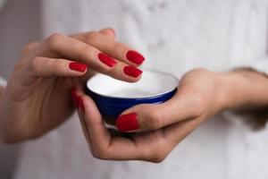handen om de crème uit de blauwe pot aan te brengen foto