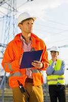 mannelijke architect met klembord werken op locatie terwijl collega staat