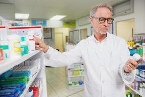 geconcentreerde apotheker die geneeskunde bekijkt foto