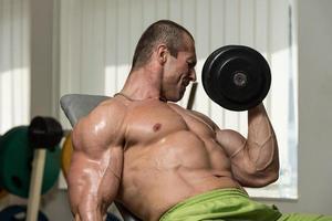 jonge man uit te werken biceps halter concentratie krullen foto