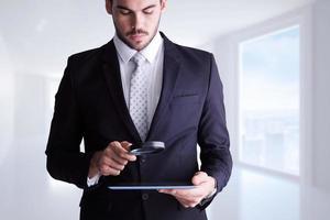 samengesteld beeld van geconcentreerde zakenman met vergrootglas foto