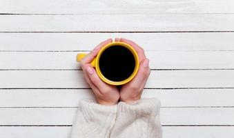 vrouwelijke handen met kopje koffie op houten tafel.