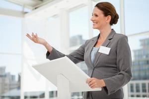 gelukkig zakenvrouw spreken op podium foto