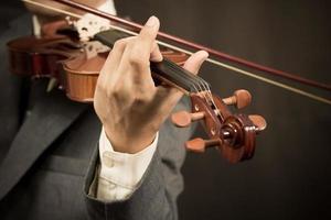 Aziatische muzikant speelt viool op donkere achtergrond foto
