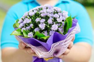 bijgesneden afbeelding van een man met boeket van paarse bloemen foto