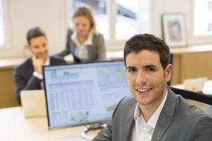 portret van knappe zakenman in moderne kantoren. uitziende camera
