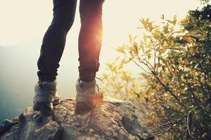 jonge vrouw wandelaar staan op zonsopgang bergtop foto