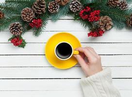 meisje met kopje koffie in de buurt van pijnboomtakken