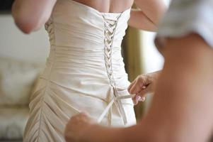 een bruid helpen om haar trouwjurk aan te trekken