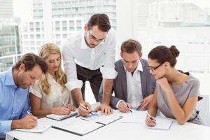 leidinggevenden schrijven van aantekeningen in het kantoor foto