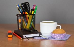 kantoorbenodigdheden, kopje koffie en gebak foto
