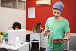 casual zakenman voor SMS-berichten in kantoor foto