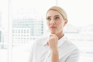 doordachte zakenvrouw wegkijken op kantoor foto