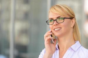 mooie zakenvrouw permanent in de buurt van kantoorgebouw foto