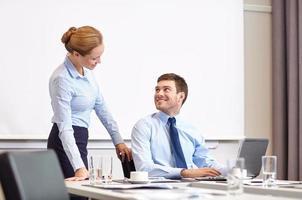 zakenman en secretaris met laptop in kantoor foto