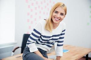 zakenvrouw zittend op de tafel in kantoor foto