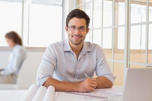 glimlachende zakenman die aan blauwdrukken op kantoor werkt foto