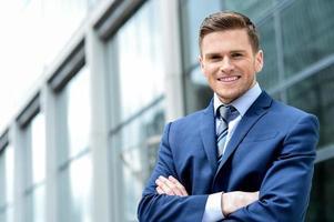 jonge zakenman glimlachend in een kantoor buiten foto