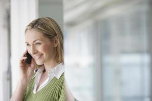 zakenvrouw met behulp van mobiele telefoon in kantoor foto