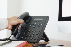 hand houdt een telefoon op kantoor foto