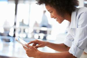 lachende jonge vrouw in een kantoor met behulp van een tablet