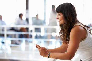 portret van glimlachende vrouw in kantoor met slimme telefoon foto
