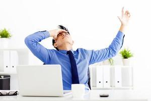 beklemtoonde zakenman die in het bureau werkt foto