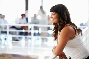 portret van glimlachende vrouw in kantoor, zijaanzicht foto