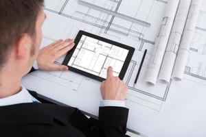 architect met behulp van digitale tablet op blauwdruk in kantoor