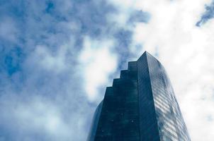 hoge wolkenkrabber kantoorgebouw met bewolkte blauwe hemel foto