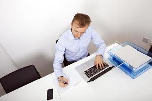 zakenman die aantekeningen maakt terwijl het gebruiken van laptop in bureau foto