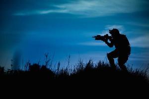 silhouet van militaire soldaat of officier met wapens 's nachts. foto