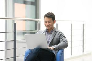 jonge Aziatische zakenman met behulp van tablet, mobiele telefoon op kantoor foto