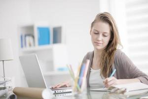 mooie jonge vrouw die op haar laptop in haar kantoor werkt foto