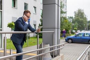 Kaukasische zakenman buiten kantoor met behulp van mobiele telefoon en tablet-pc.