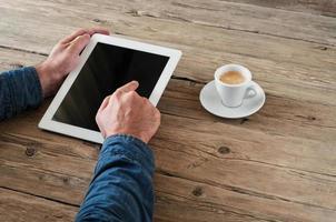 mannen drukt op de leeg scherm tablet-computer voor houten kantoor foto