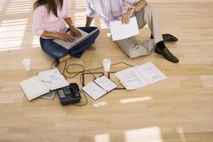 zakenpartners zittend op de vloer in kantoor, vrouw met behulp van laptop foto