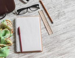 open een blanco notitieblok, pen, bril, handtas en sjaal foto